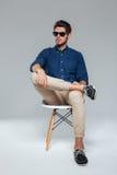 Homme décontracté bel dans les suglasses se reposant sur la chaise Image stock