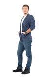 Homme décontracté de sourire dans les jeans et la chemise de denim avec des mains dans des poches Image libre de droits