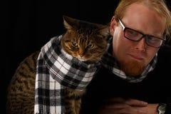 Homme décontracté s'asseyant avec le chat dans son écharpe Image libre de droits