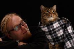 Homme décontracté s'asseyant avec le chat dans son écharpe DOF peu profond Photos stock