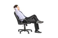 Homme décontracté s'asseyant dans une chaise de bureau Photo libre de droits