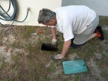 Homme découvrant la soupape d'arrêt de l'eau Images libres de droits