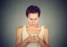 Homme dégoûté lisant un message textuel Photographie stock libre de droits