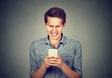 Homme dégoûté lisant un message textuel Photographie stock
