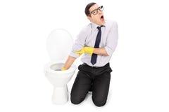 Homme dégoûté nettoyant une toilette avec des gants de nettoyage Images stock