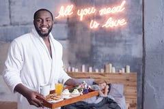 Homme délicieux d'Afro-américain tenant le plateau de petit déjeuner dans la chambre à coucher Images stock