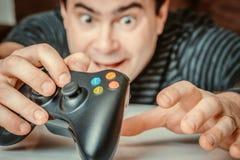 Homme dépendant émotif jouant des jeux vidéo photo stock