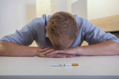 Homme dépendant avec une cigarette cassée Images libres de droits