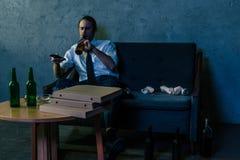 homme dépendant d'alcool déprimé dans la chemise blanche regardant la TV et buvant de la bière images libres de droits