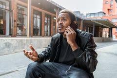 Homme désagréable étonné et contrarié à la peau foncée parlant par le téléphone portable photographie stock