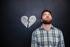 Homme désespéré se tenant au-dessus du fond de tableau noir avec le coeur brisé tiré Image libre de droits