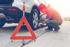Homme détachant des écrous de crochet sur son pneu crevé de voiture photos stock