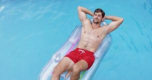 Homme détendant avec des mains derrière la tête sur le tube gonflable dans la piscine 4k banque de vidéos