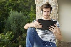 Homme détendant avec le PC de comprimé photographie stock libre de droits