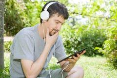 Homme détendant avec le PC de comprimé photos stock
