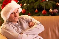Homme détendant devant l'arbre de Noël Photographie stock libre de droits