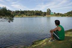 Homme détendant par le lac Photo stock
