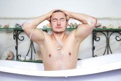 Homme détendant prenant un bain mousseux Les lavages écument de la tête Concept de sexualité et de relaxation Type dans la salle  photos libres de droits