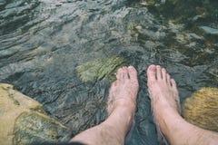 Homme détendant ses pieds dans la cascade froide et fraîche photo libre de droits