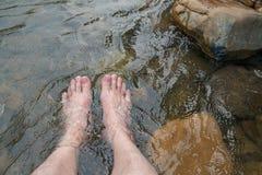 Homme détendant ses pieds dans la cascade froide et fraîche photographie stock