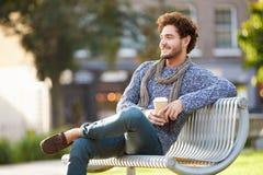 Homme détendant sur le banc de parc avec du café à emporter Image libre de droits