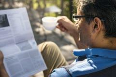 Homme détendant tout en lisant un journal Photos libres de droits