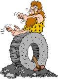 Homme d'âge de pierre s'asseyant sur une roue en pierre Image stock