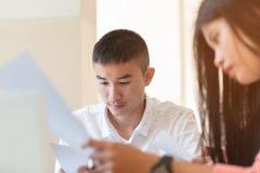 Homme d'étudiants ou groupes de travail asiatiques de jeune entreprise avec le document Photos libres de droits