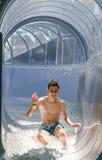 Homme d'adolescent descendant une glissière d'eau Image stock