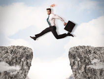 Homme d'affaire louche sautant par-dessus des roches avec l'espace Photo libre de droits