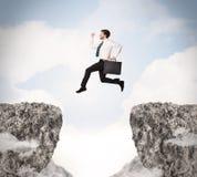 Homme d'affaire louche sautant par-dessus des roches avec l'espace Images libres de droits