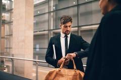 Homme d'affaires à l'aéroport avec le sac regardant sa montre Photo libre de droits