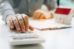 Homme d'affaires à l'aide de la calculatrice pour calculer le budget au sujet de l'hypothèque de contrat de maison dans la salle  photos stock