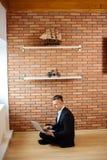 Homme d'affaires à l'aide de l'ordinateur portable à la maison tout en se reposant sur le plancher Photos stock