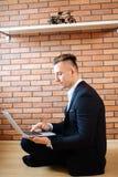 Homme d'affaires à l'aide de l'ordinateur portable à la maison tout en se reposant sur le plancher Photographie stock libre de droits