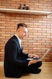 Homme d'affaires à l'aide de l'ordinateur portable à la maison tout en se reposant sur le plancher Images libres de droits