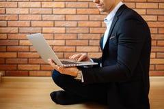 Homme d'affaires à l'aide de l'ordinateur portable à la maison tout en se reposant sur le plancher Images stock