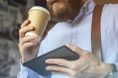 Homme d'affaires à l'aide du comprimé numérique et buvant du café pour aller dehors Concept de pause-café photo stock