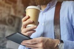 Homme d'affaires à l'aide du comprimé numérique et buvant du café pour aller dehors Concept de pause-café photo libre de droits