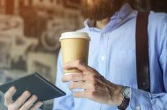 Homme d'affaires à l'aide du comprimé numérique et buvant du café pour aller dehors Concept de pause-café photographie stock libre de droits