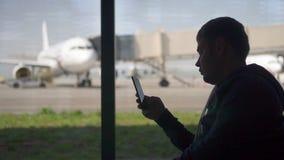 Homme d'affaires à l'aide du téléphone à l'aéroport Silhouette d'un voyageur d'homme clips vidéos
