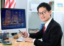 Homme d'affaires à l'aide du téléphone et de l'ordinateur portable intelligents dans le bureau images stock