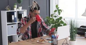 Homme d'affaires à l'aide du téléphone portable et de l'ordinateur portable tout en buvant du café au bureau banque de vidéos