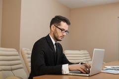 Homme d'affaires à une dactylographie d'espace de travail Image stock