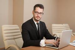 Homme d'affaires à une dactylographie d'espace de travail Photo stock