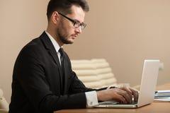 Homme d'affaires à une dactylographie d'espace de travail Image libre de droits