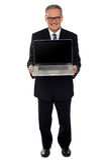 Homme d'affaires âgé affichant l'ordinateur portatif neuf lancé Image libre de droits