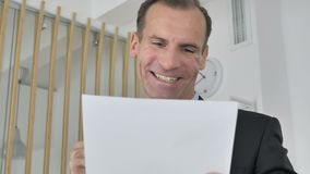 Homme d'affaires âgé moyen Celebrating Success tout en lisant des documents dans le bureau banque de vidéos