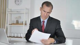 Homme d'affaires âgé moyen Reading Documents dans le bureau banque de vidéos