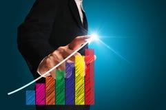 Homme d'affaires écrivant au-dessus de l'histogramme d'accomplissement Image stock
